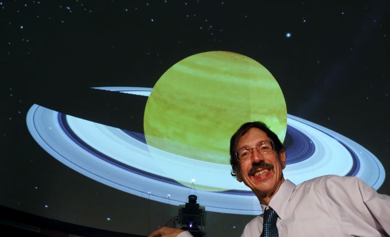 by: COURTESY OF PAT HANRAHAN - Pat Hanrahan, MHCC Planetarium director, stands in front of a dome display of Saturn. The Planetarium allows you to view different perspectives of the planets and their orbits around the sun.