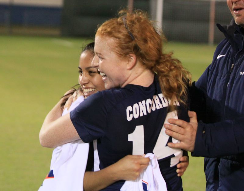by: COURTESY OF CONCORDIA UNIVERSITY - Hannah Scott (right) gets a hug from teammate Jasmin Ayala after Concordias NAIA title game victory. Scott was voted the most outstanding offensive player at the national tournament, and Ayala was named tourney MVP.