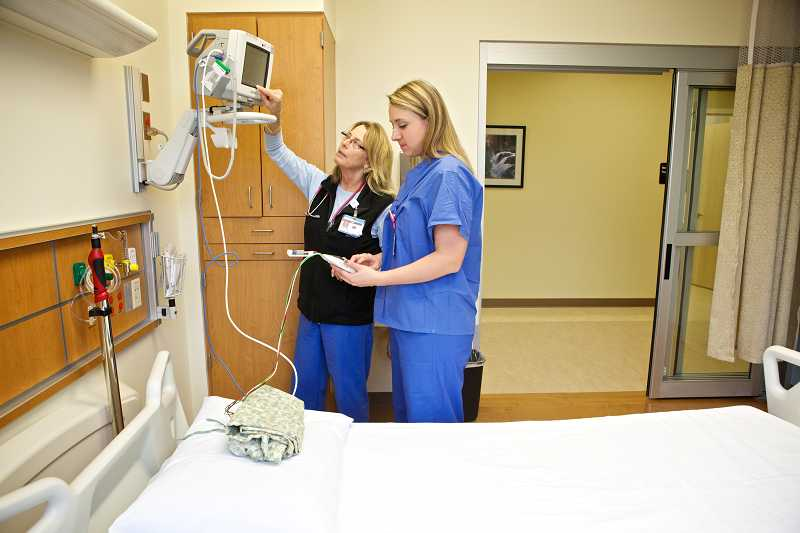 by: JAIME VALDEZ - Legacy Meridian Park Medical Center Chest Pain Center nurses Nan Beckwith and Kristen Ash adjust a telemetry cardiac monitor.