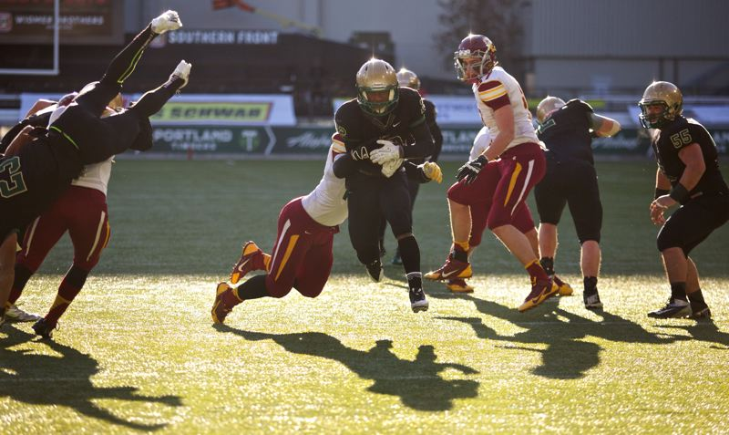 by: TIMES PHOTO: JAIME VALDEZ -  Jesuit Crusaders running back Chase Morrison (22) runs by Central Catholic Rams' Matt Vanoudenhaegen (42) and Derek Reed (9) in the 6A football championship at Jeld-Wen Field.