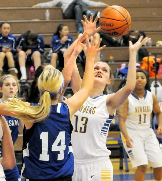 by: SETH GORDON - Within reach - Heather Petrie fights for a rebound during Newberg's 42-35 win over Gresham Friday. Petrie finished with eight points in what head coach Tamie Woginrich called 'the best basketball I've ever seen her play.'