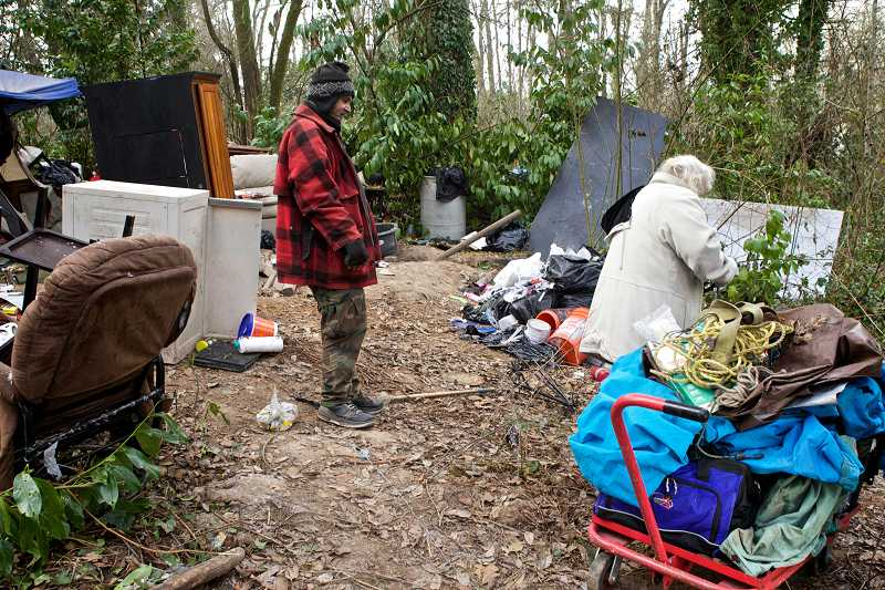 by: JAIME VALDEZ - Residents of a homeless camp near Tigard Cinemas survey their campsite. Tigard Police have cleared out the camp and will spend the next several days throwing away couches, dressers, doors, insulation and other items left behind.