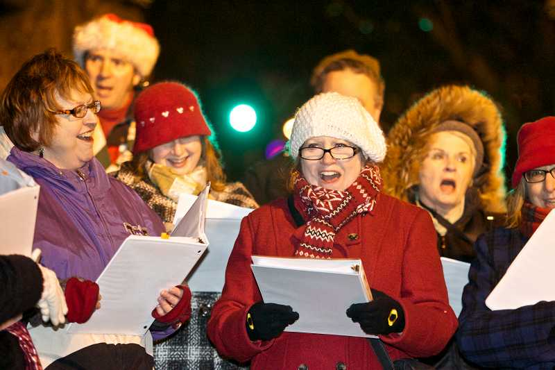 by: TIMES PHOTO: JAIME VALDEZ - The Mask and Mirror Singers, accompanied by the Tualatin Valley Community Band, perform during the Tigard Tree Lighting on Friday night.