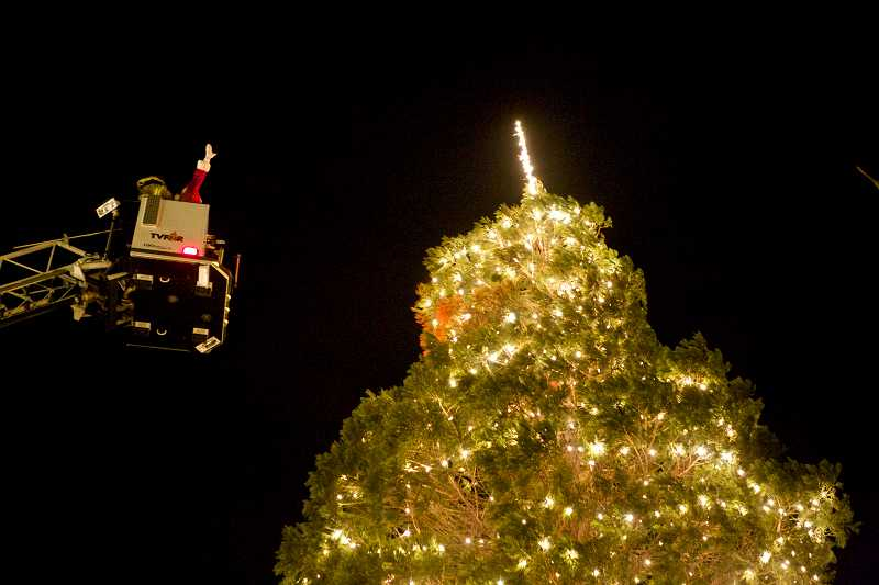 by: TIMES PHOTO: JAIME VALDEZ - Santa Claus waves to the crowd below while on a Tualatin Valley Fire & Rescue ladder truck after lighting the star on the Tigard Christmas tree.