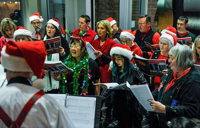 by:  TIMES PHOTO: JOHN LARIVIERE - The City of Beaverton Staff Choir entertains guests with carols in the Beaverton City Library during Friday night's Holiday Open House.