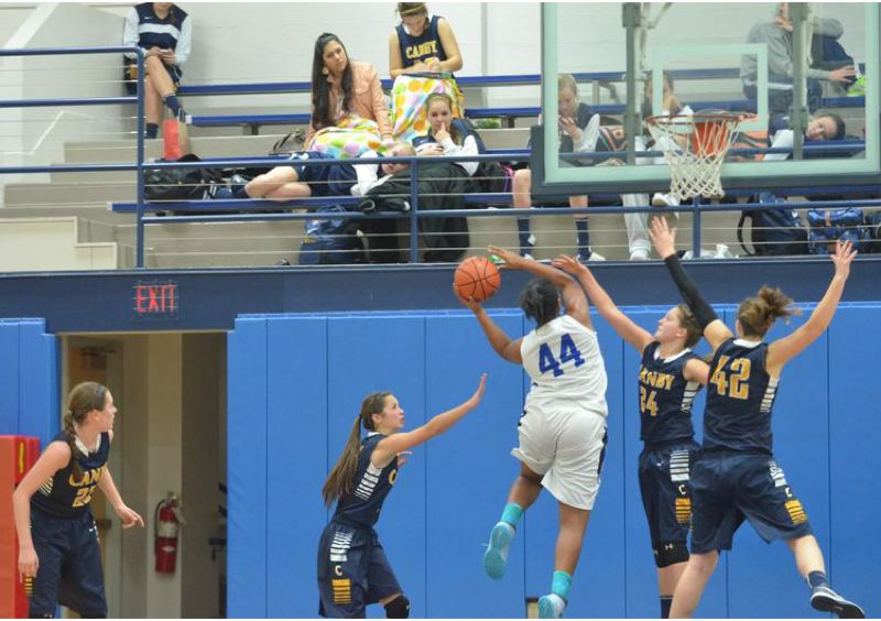 by: PAMPLIN MEDIA GROUP: JEFF GOODMAN - The Canby Cougars try to collapse on Tyschal Blake of St. Mary's Academy as she goes for an inside score.