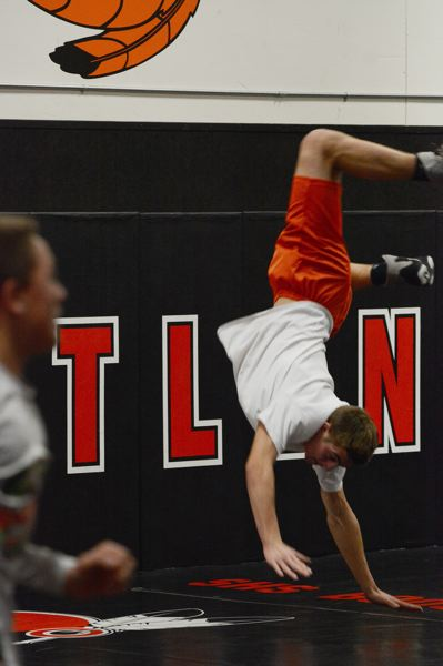 by: JOHN WILLIAM HOWARD - Junior Johnny Tardiff completes a flip during warm ups. Not one of the 'weight-cutting' programs, the Indians get to their weight by wrestling and good nutrition instead of losing water weight and over conditioning.