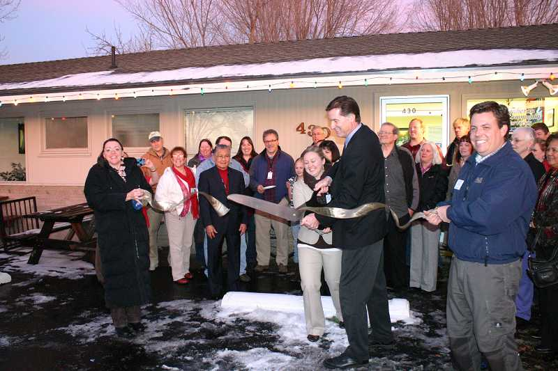 by: JASON CHANEY - Brian Dement, Lutheran Community Services Program Director II, cuts the ribbon at the service's new resource center during a recent open house.
