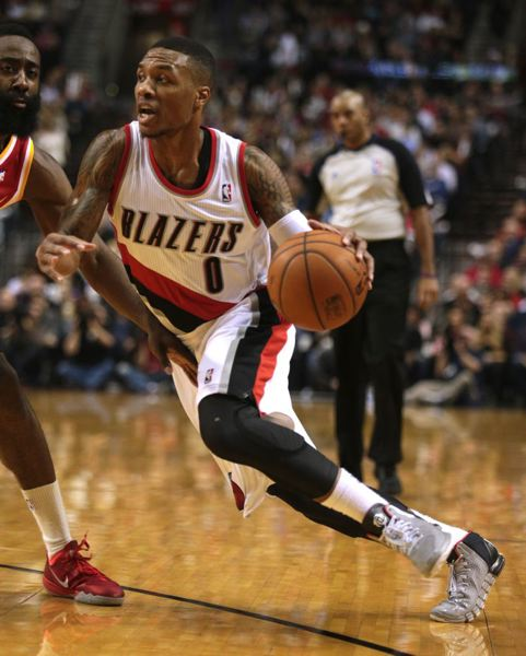Damian Lillard tries to drive on Houston's James Harden.