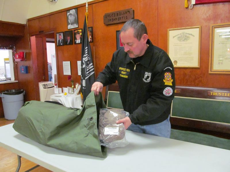by: PHOTO BY ELLEN SPITALERI - VFW Post #1324 Commander Ken Kraft packs a duffel bag full of supplies to give to homeless vets, just one of the services offered by his organization.