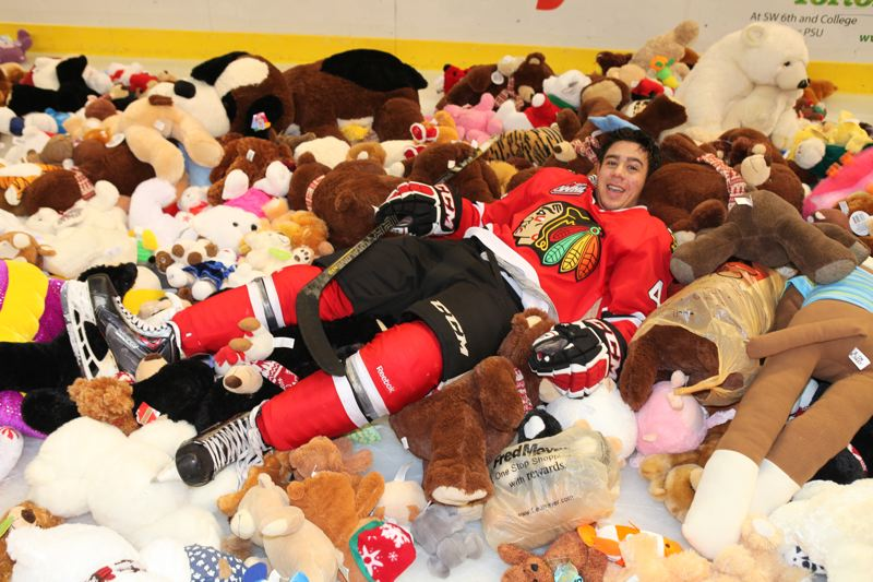 by: COURTESY OF PORTLAND WINTERHAWKS - Keoni Texeira of the Portland Winterhawks finds a soft spot to rest for a moment after his first Western Hockey League goal triggered the annual Teddy Bear Toss at Memorial Coliseum.
