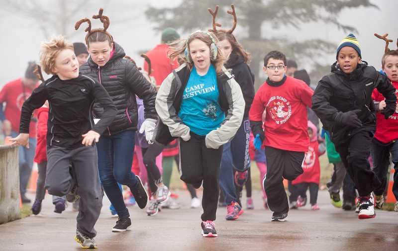 by: JOSH KULLA - About 300 people showed up on a foggy, chilly Saturday morning for the city of Wilsonvilles inaugural Reindeer Romp through the middle of the city. Participants included the youngest children to active seniors, and there were plenty of families enjoying a morning of exercise together.