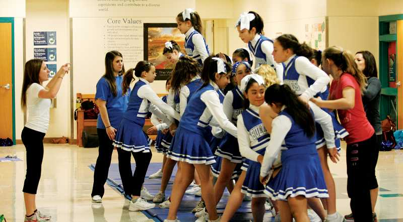 by: PHIL HAWKINS - The Junior Bulldogs cheer team works on their routine during Friday's dress rehearsal at Valor Middle School. At left is cheer coach Erica Bailey, one of five coaches who have volunteered to help instruct the team. Bailey is a Woodburn High School graduate and current student at Portland State University.