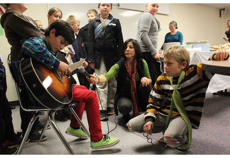 by: MAYGAN BECKERS - Fifth grade Jonathan Swenson plays guitar, as Alejandra Clemens, Swenson's mother, holds the microphone for parents and students to listen while they fill their plates with Russian food.