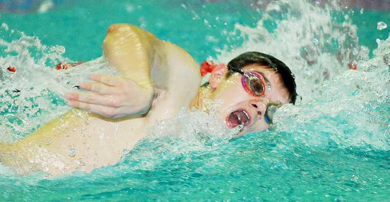 by: SETH GORDON - Getting a lungfull - Bjorn Larsen twists as he nears the wall during the 100 backstroke even Thursday at the Chehalem Aquatic Center. Larsen won the event as the Tiger boys beat McMinnville for the first time since 2007.