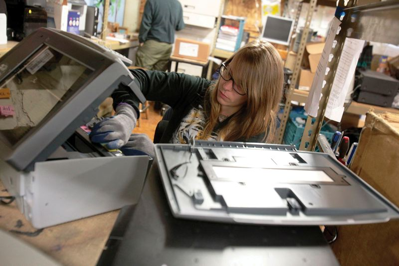 by: PAMPLIN MEDIA GROUP: JONATHAN HOUSE - Amber Schmidt of Free Geek in Portland checks out a donated printer to see if its worth salvaging.