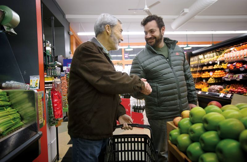 by: PAMPLIN MEDIA GROUP: JONATHAN HOUSE - Paul greets Food Front produce buyer and merchandiser Josh Alsberg at the stores Northwest location.