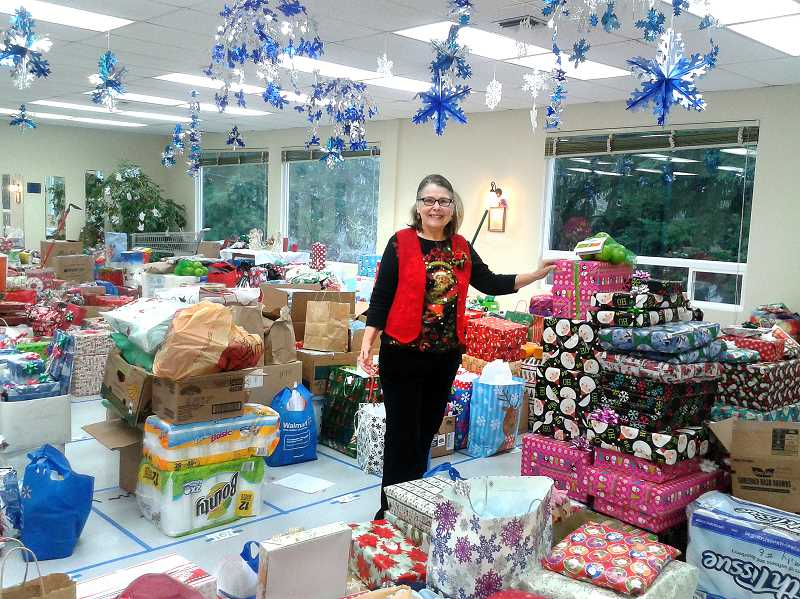 by:  ISABEL GAUTSCHI - Janet Kiger-Hellard leads the way through a room full of gifts awaiting 138 local families.