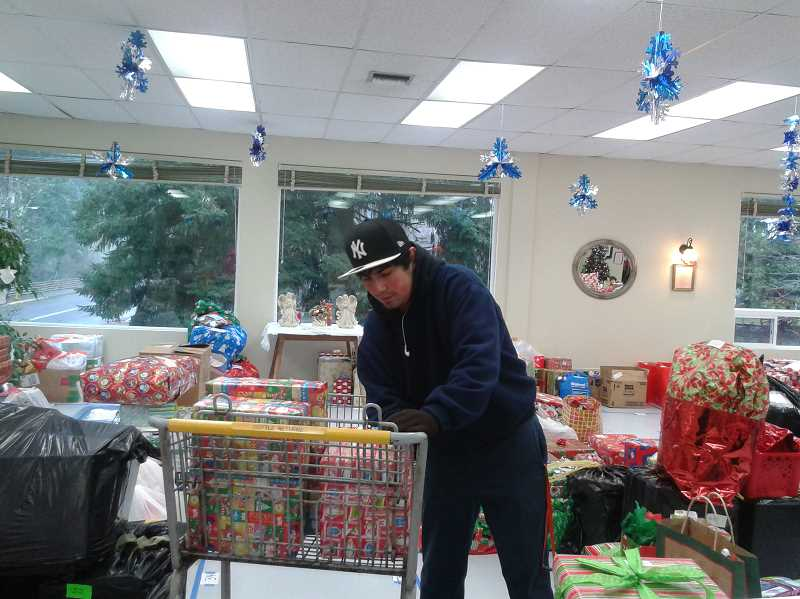 by: ISABEL GAUTSCHI - Leo Milner, a volunteer from Timberlake Job Corps, prepares to bring presents to one of the adopted families.
