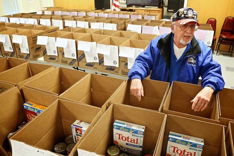 by: TIMES PHOTO: JAIME VALDEZ - Bob Sullivan, commander of Tigard American Legion Post 158, says the group is wrapping up 130 boxes of food and gifts to deliver to area families and veterans.