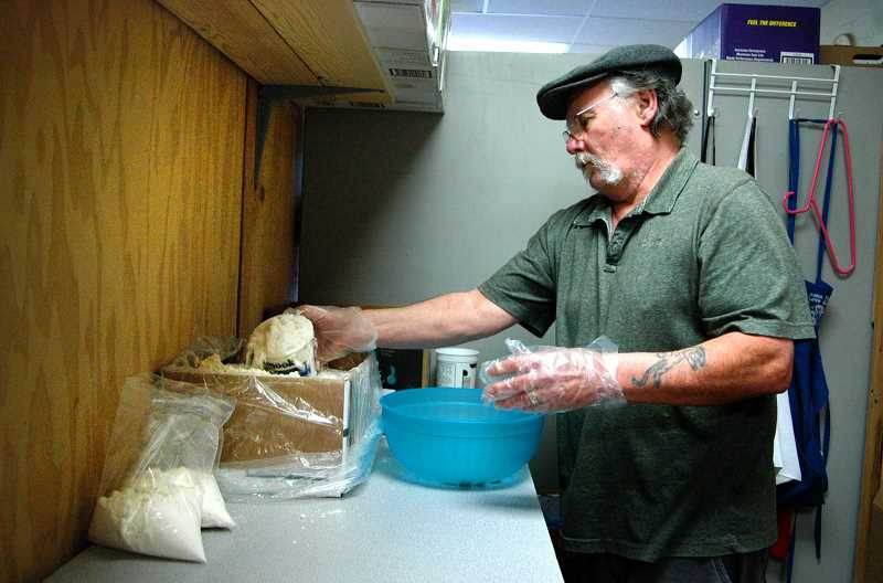 by: ISABEL GAUTSCHI - Volunteer Mike Varn repackages bulk pancake flour into smaller portions.