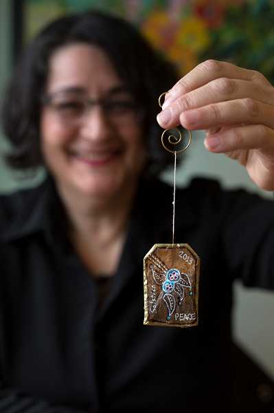 by: TIMES PHOTO: JONATHAN HOUSE - Artist Toni Curry holds one of her tea bag Christmas tree ornaments at Medley Tea House in Multnomah Village.