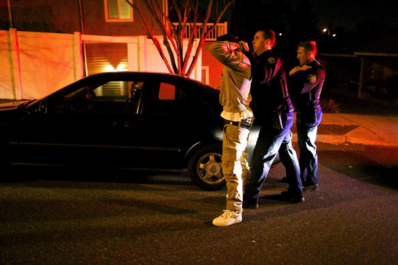 by: TRIBUNE PHOTO: JAMIE VALDEZ - Gang Enforcement Team officer Patrick Murphy -- after asking permission -- pats down a young black man who had been sitting in a parked car on Southeast 119th Avenue. Officer Brian Dale looks on. Frisking for weapons is expected to increase as Portlands new hot spot policing program puts more officers on foot in high-crime areas.