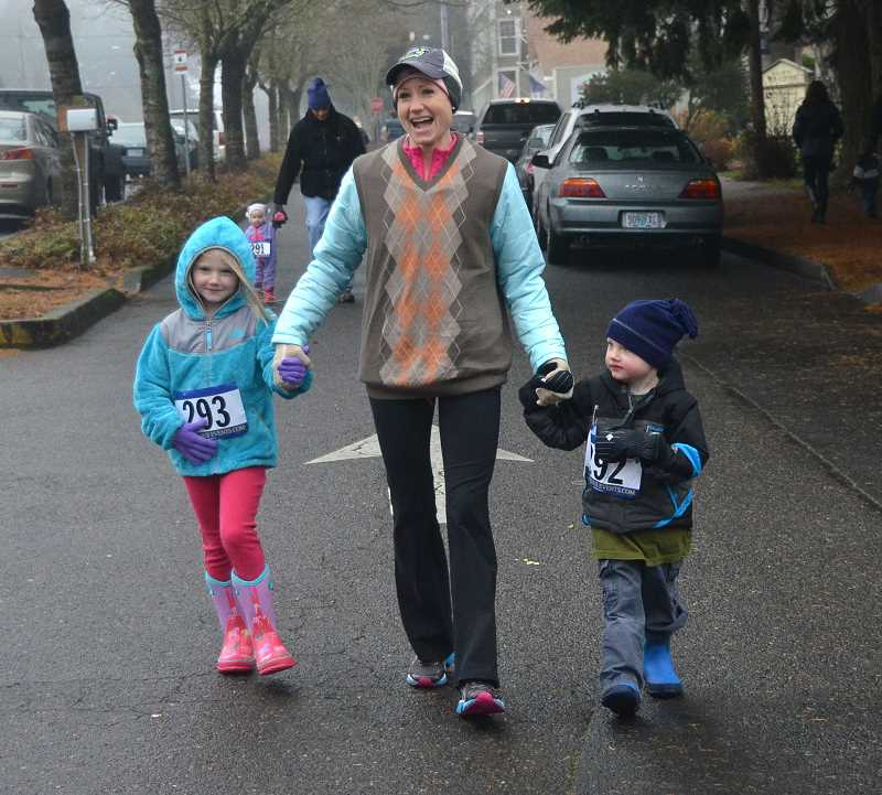 From left, Evelyn, 6, Melissa, and Nicholas, 3, Morlan of West finish up the 1 mile Ugly Sweater run.