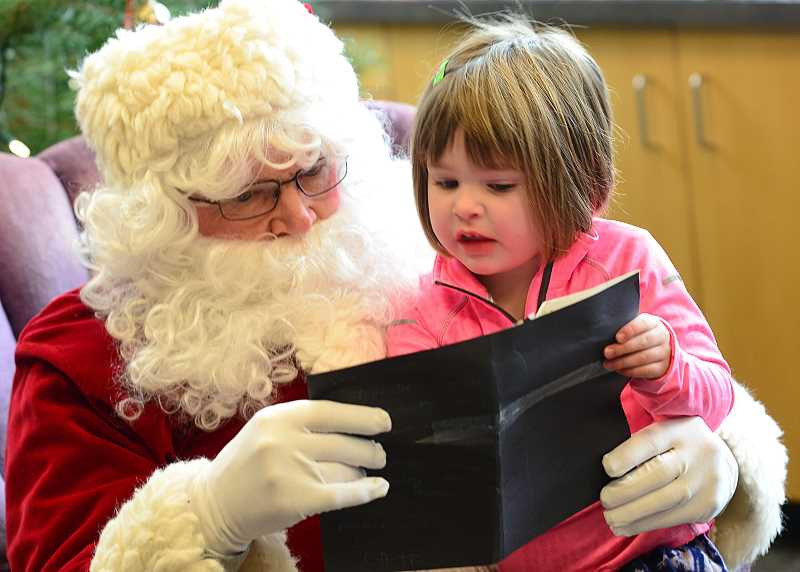 Kate Munzii, 4, of West Linn goes over her list with Santa.
