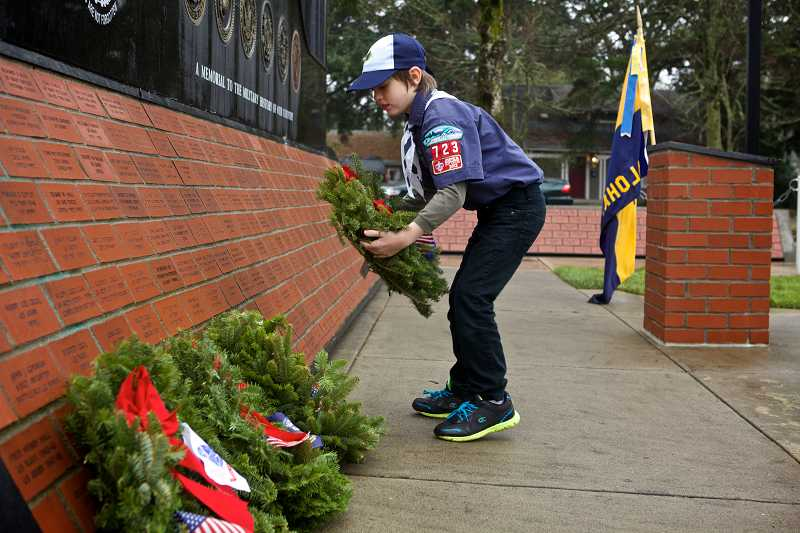 by: TIMES PHOTO: JAIME VALDEZ - Thomas Hochstetler, a Cub Scout from Pack 723, places a wreath at Beaverton's Veterans Memorial Park during a Wreaths Across America event held Dec. 14.