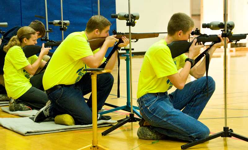 by: LON AUSTIN/CENTRAL OREGONIAN - CCHS NJROTC squad members Mallory Sowers, Justin Bozarth, and Joe Gerke compete in the kneeling target practice during the event. Although the team did not place they improved their performance by 25 percent.