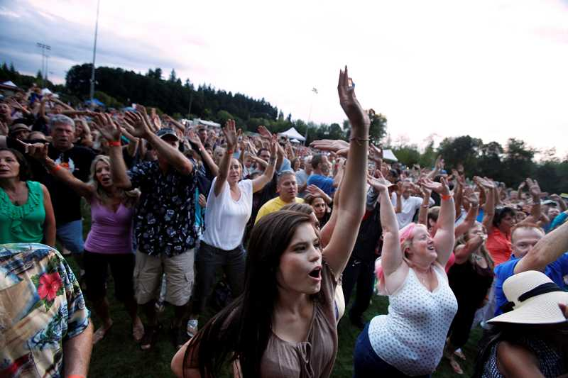by: TIMES PHOTO: JONATHAN HOUSE - An energetic crowd sings along to Journey cover band Stone in Love's rendition of 'Faithfully,' during the Tualatin Hills Park and Recration District's annual Groovin' on the Grass concert. The park district secured a $1,500 grant for its summer concerts and theater productions in the park series.