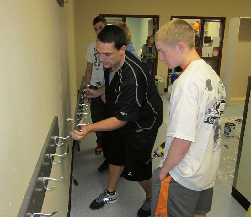 by: BARBARA SHERMAN - Sherwood High School head football coach Greg Lawrence reattaches a coat rack to a newly painted wall in the special needs classroom, while sophomore Colton Buchanan, a football player, looks on.