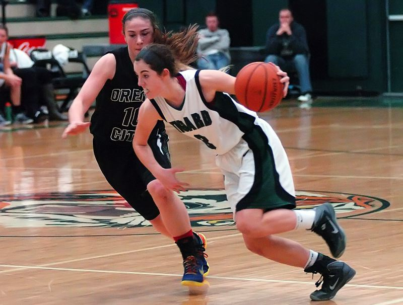 by: DAN BROOD - MOVING FAST -- Tigard High School senior guard Emilee Cincotta (right) drives past Oregon City's Cierra Walker in Friday's game. The Pioneers scored a 68-47 victory.