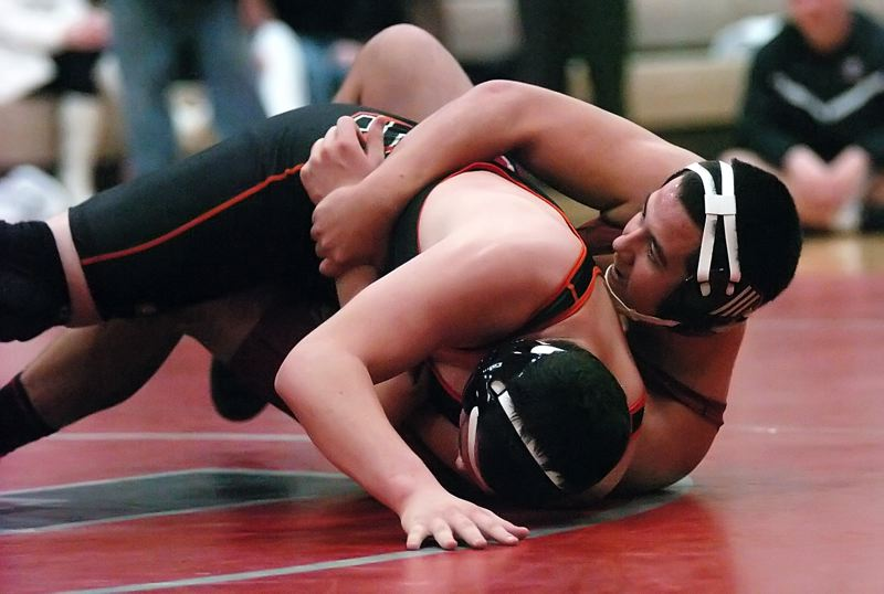 by: DAN BROOD - TAKING CHARGE -- Tualatin High School junior Kellen Poti (right) looks to roll Sprague's Justin Ellis during their 220-pound match last week. Poti scored a 9-8 decision victory.