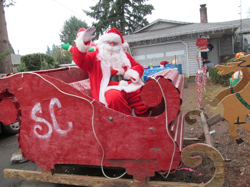 by: PHOTO BY ELLEN SPITALERI - Keith McDonley, in costume as Milwaukie Santa, is a familiar sight to motorists passing by his home on Southeast Clackamas Road. He handed out more than 70 free Christmas trees this year.