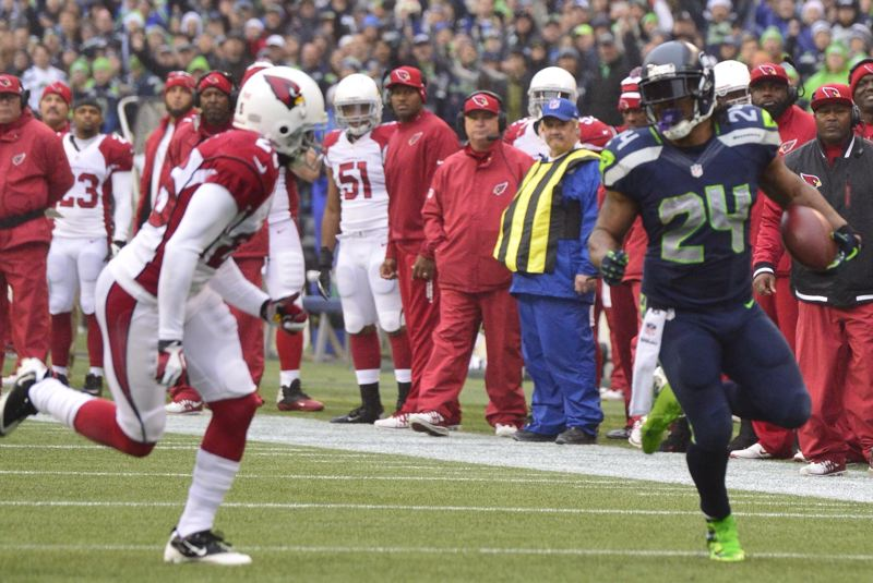Marshawn Lynch of Seattle (right) picks up some yardage against Arizona.