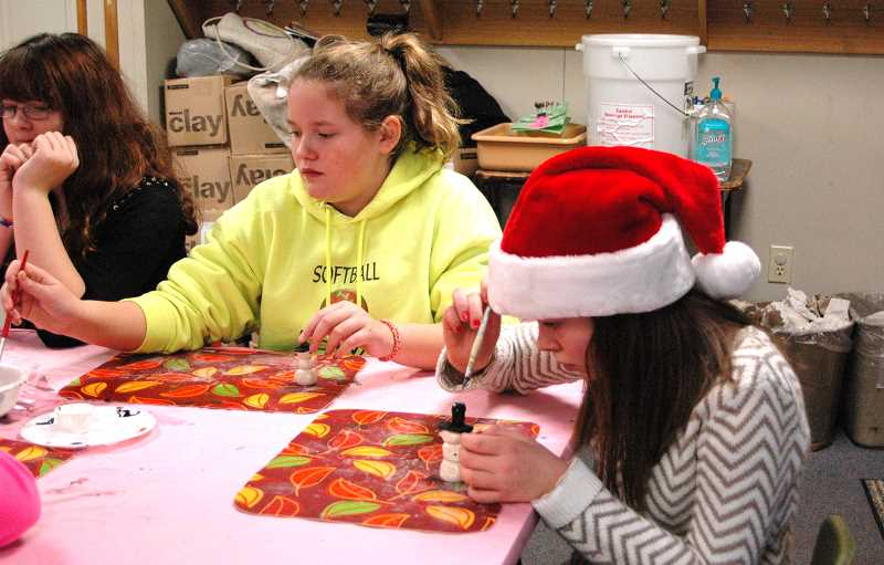 by:  ISABEL GAUTSCHI -  Allison Andersen (from left), Ryann Curtis and Abby Astanin get serious about painting the clay snowmen.