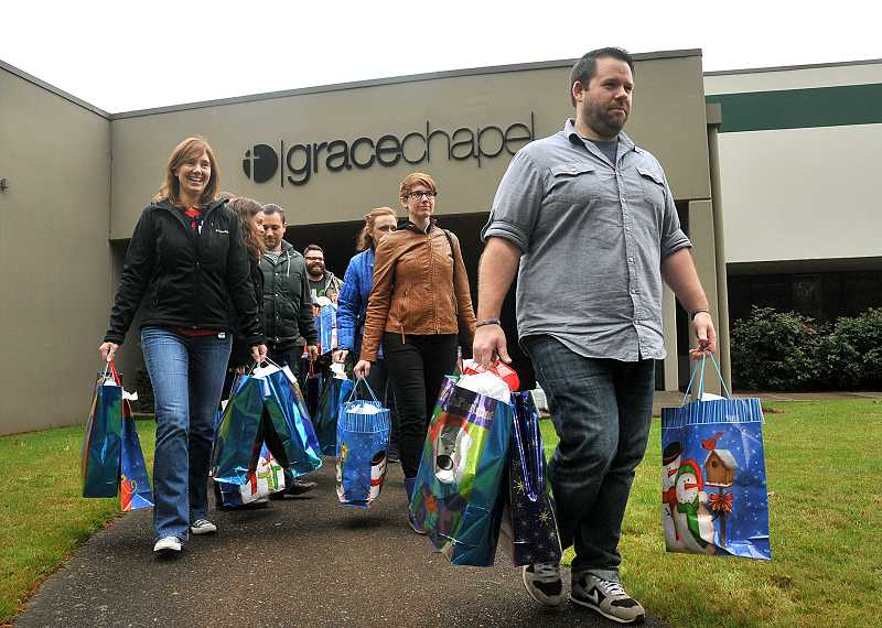 by: PAMPLIN MEDIA GROUP: VERN UYETAKE - Jake Schwein leads a procession of church workers and volunteers. They are carrying gifts that were delivered to children in need in Wilsonville.
