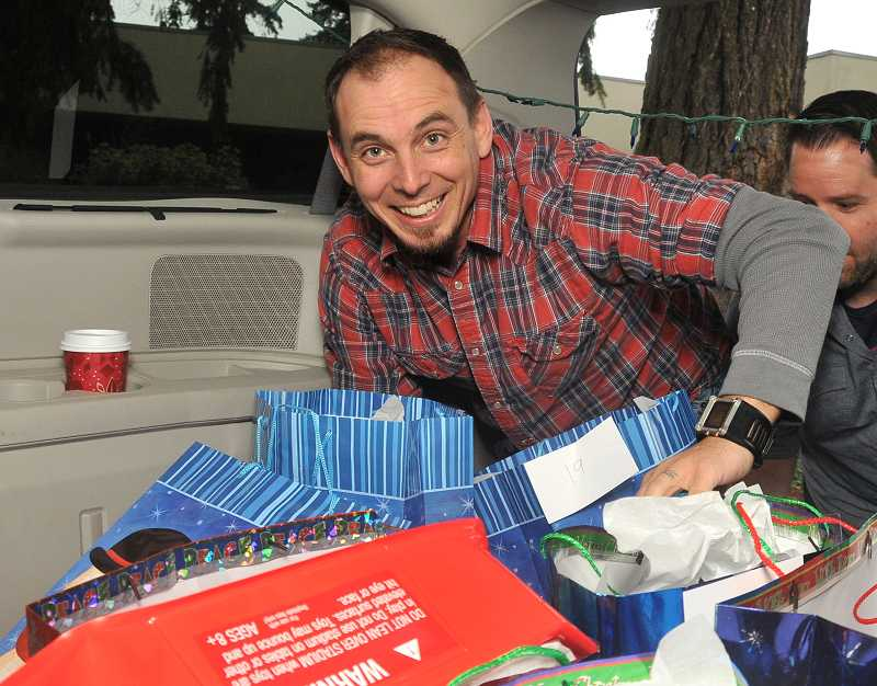 by: PAMPLIN MEDIA GROUP: VERN UYETAKE - Mike Tatlock, lead pastor at Grace Chapel, loads packages into the back of his wife Bernadettes car.