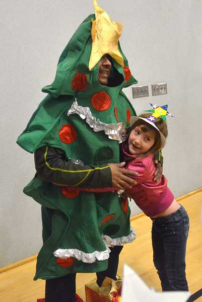 by: TIDINGS PHOTO: VERN UYETAKE - Felix Rosario, Boltons building engineer, dressed as a holiday tree, earns a hug from first-grader Madalyn Hersy.