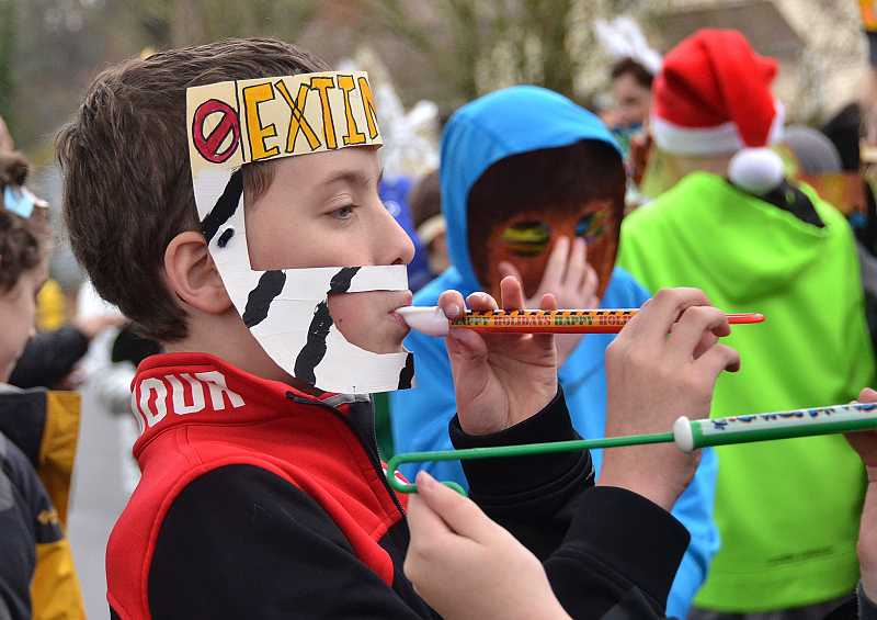 by: TIDINGS PHOTO: VERN UYETAKE - Fifth-grader Mason Price adds some noise to the parade with his slide whistle.