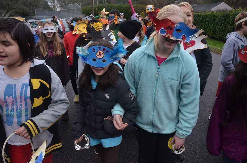 by: TIDINGS PHOTO: VERN UYETAKE - Fifth-graders Kirsten Nordstrom, left, and Hannah Strobe enjoy their final parade at Bolton.