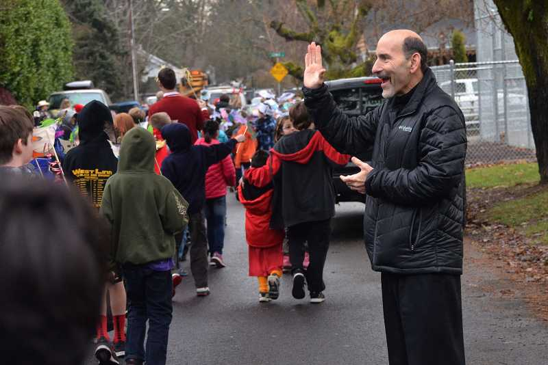 by: TIDINGS PHOTO: VERN UYETAKE - West Linn-Wilsonville Superintendent Bill Rhoades waves as the parade passes him.