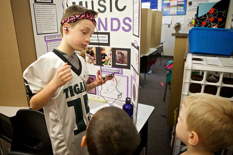 by: TIMES PHOTOS: JAIME VALDEZ - Jack Briggs, 11, shows youngsters a headband he invented with headphones built into the lining during the Invention Convention at Charles F. Tigard Elementary School.