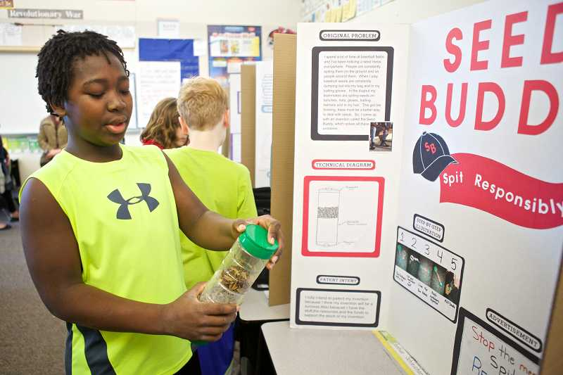 by: TIMES PHOTOS: JAIME VALDEZ - Josh Schleichardt, 11, holds a canister he invented that baseball players can spit sunflower seeds into during the Invention Convention at Charles F. Tigard Elementary School.