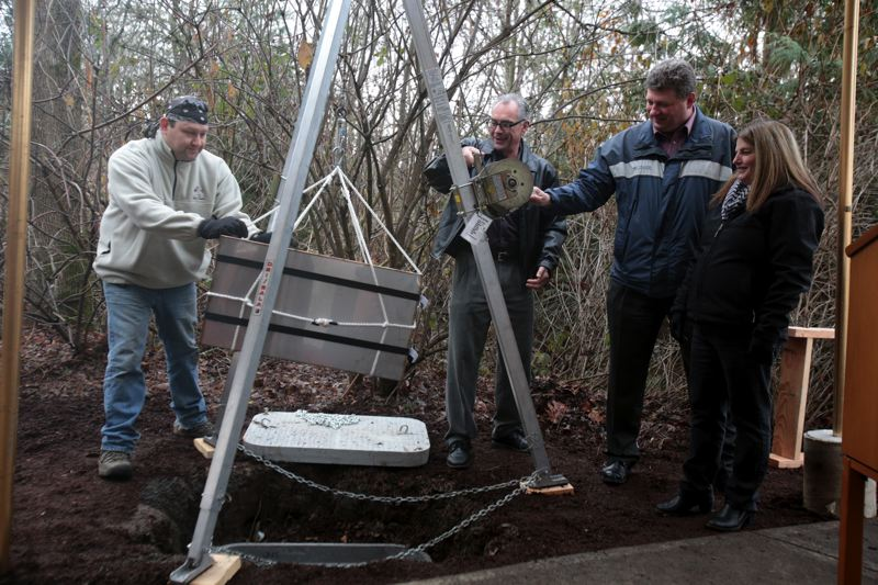 by: TIMES PHOTO: JONATHAN HOUSE - Tualatin Mayor Lou Ogden, center, along with City Council members Frank Bubenik and Monique Beikman, lower a time capsule that will be unearthed in 50 years.