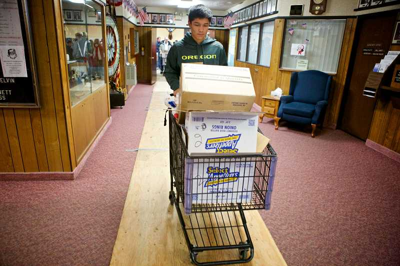 by: TIMES PHOTO: JAIME VALDEZ - Joe Hernandez, a sophomore at Sunset High School, pushes a shopping cart with boxes of food and toys to be delivered to the needy during the annual Beaverton Elks Lodge Christmas Basket Delivery.