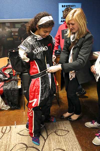 by: TIMES PHOTO: JAIME VALDEZ - Dani Ferrara, 22, who is a race car driver from Vancouver, Wash., helps Marea Hines, 12, try on a racing suit that Cindi Lux wears when racing.
