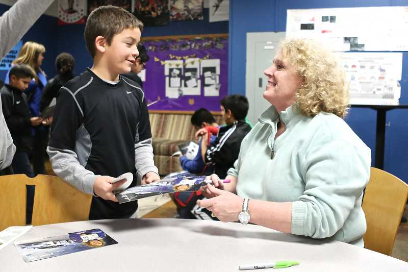 by: TIMES PHOTO: JAIME VALDEZ - Cindi Lux, a professional race-car driver from Aloha, signs an autograph for Beaverton Police Activities League member Robert Aleman, 10.